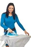 Smiling woman ironing a shirt stock image