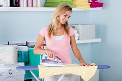 Smiling Woman Ironing T-shirt On Ironing Board Stock Image