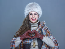 Smiling woman isolated on cold blue showing heart shaped hands. Winter things. Portrait of smiling modern woman in fur hat isolated on cold blue showing heart Stock Images