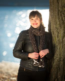 Smiling woman in jacket posing on riverbank at autumn sunny day Royalty Free Stock Photo
