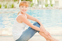 Smiling woman in jeans nearby pool Royalty Free Stock Images