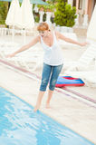 Smiling woman in jeans nearby pool Stock Photo