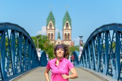 Smiling woman jogging across an urban bridge. Smiling woman jogging across an arched urban bridge approaching the camera in spring sunshine in a fitness and stock photos