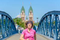 Smiling woman jogging across an urban bridge. Smiling woman jogging across an arched urban bridge approaching the camera in spring sunshine in a fitness and royalty free stock photo