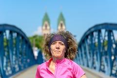 Smiling woman jogging across an urban bridge. Close up of an Smiling woman jogging across an arched urban bridge approaching the camera in spring stock images