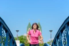 Smiling woman jogging across an urban bridge. Low angle view of an Smiling woman jogging across an arched urban bridge stock image