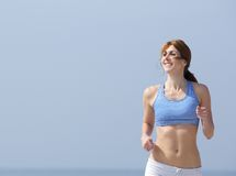 Smiling woman jogging outdoors Royalty Free Stock Image