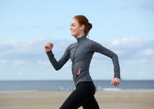 Smiling woman jogging at the sea side Royalty Free Stock Photo