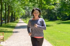 Smiling woman jogging towards the camera. In a park in a healthy active lifestyle concept royalty free stock photo