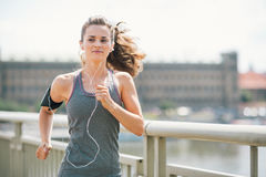Smiling woman jogging in urban setting listening to music Royalty Free Stock Image