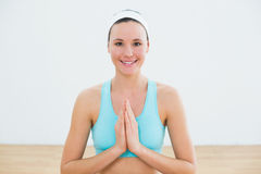 Smiling woman with joined hands at fitness studio Royalty Free Stock Photography