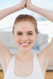 Smiling woman with joined hands over head Royalty Free Stock Photography