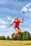 Smiling woman jumping with cell phone for self-portrait Royalty Free Stock Image