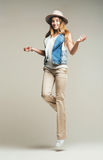 Smiling woman jumping in denim waistcoat and hat Stock Photos