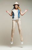 Smiling woman jumping in pants and denim waistcoat Royalty Free Stock Photos