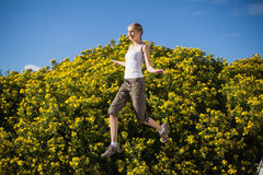 Smiling woman jumping beside yellow flowers Stock Image
