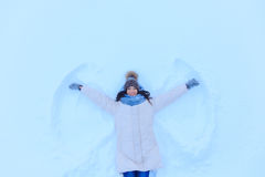 Smiling woman kidding on snow in winter. Young smiling woman kidding on snow in winter day Royalty Free Stock Image