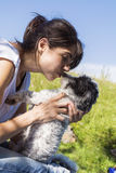 Smiling woman kissing her white  dog outdoor Royalty Free Stock Photography