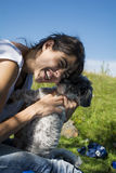 Smiling woman kissing her white  dog outdoor Stock Photo