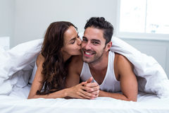 Smiling woman kissing man while lying under blanket Stock Images