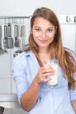 Smiling woman in the kitchen drinking milk Stock Photos