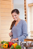 Smiling woman in the kitchen slicing vegetables Stock Photo
