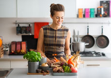 Smiling woman in kitchen sorting autumn vegetables Royalty Free Stock Images