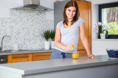 Smiling woman in kitchen squeezing orange. Smiling woman in modern kitchen squeezing orange Royalty Free Stock Photography