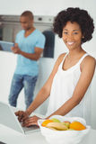 Smiling woman in the kitchen using laptop Royalty Free Stock Image
