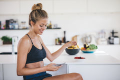 Smiling woman in kitchen using mobile phone Royalty Free Stock Photos