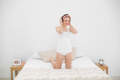 Smiling woman kneeling on her bed and wearing headphones Royalty Free Stock Image