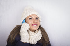 Smiling woman in knit winter clothing speaking mobile Stock Photography