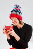 Smiling woman in knitted hat holding cup Royalty Free Stock Photos