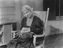 Smiling woman knitting in her rocking chair Stock Photo