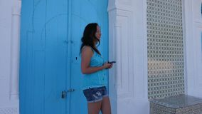 Smiling woman knocking in blue arabian door and holding phone. Woman rat tat tat to door. Smiling woman knocking in blue door and holding phone. Female person stock video