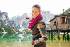 Smiling woman at Lake Bries aiming digital camera at Dolomites Stock Images