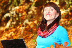 Smiling woman with laptop in autumn park Royalty Free Stock Photography