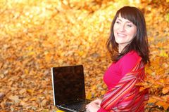 Smiling woman with laptop in autumn park Stock Photos