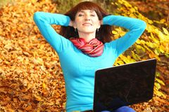Smiling woman with laptop in autumn park Stock Images