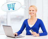 Smiling woman with laptop computer and credit card. Online shopping, people and technology concept - smiling young woman with laptop computer, credit card and Royalty Free Stock Image