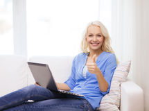 Smiling woman with laptop computer at home. Home, technology, gesture and internet concept - smiling woman sitting on the couch with laptop computer at home stock image