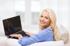 Smiling woman with laptop computer at home. Home, technology and internet concept - smiling woman sitting on the couch with laptop computer at home stock photos