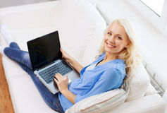 Smiling woman with laptop computer at home. Home, technology and internet concept - smiling woman sitting on the couch with laptop computer with blank black stock images