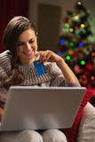 Smiling woman with laptop and credit card near christmas tree Royalty Free Stock Photo
