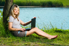 Smiling woman with laptop girl sitting under tree Royalty Free Stock Image
