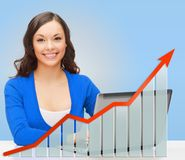 Smiling woman with laptop and growth chart Stock Photo
