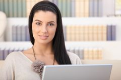 Smiling woman with laptop at home Royalty Free Stock Photography