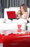 Smiling woman with laptop at home. Young smiling woman with laptop at home stock photography