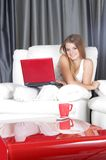 Smiling woman with laptop at home. Young smiling woman with laptop at home stock images