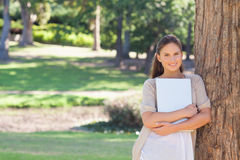 Smiling woman with a laptop leaning against a tree Royalty Free Stock Images